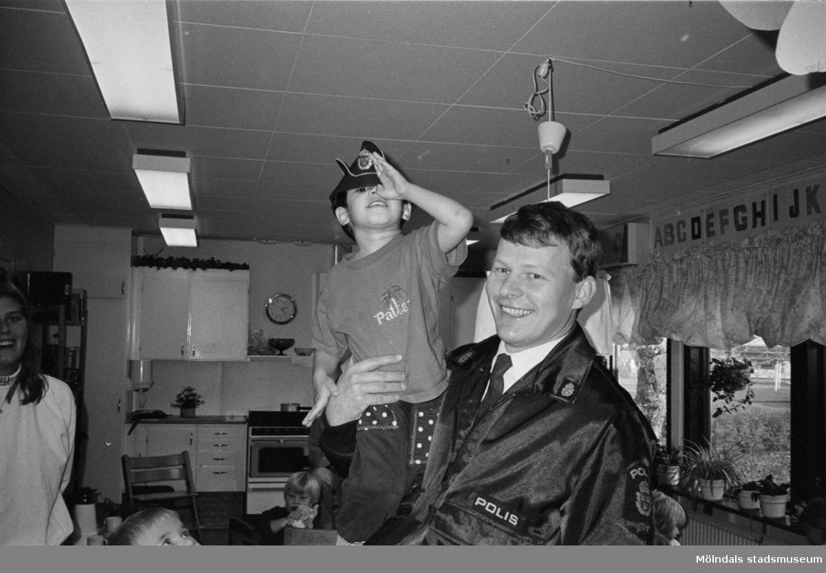 En uniformsklädd polis håller en pojke i famnen. Båda tittar leende mot kameran. Pojken har polismannens mössa på sitt huvud. De står i Katrinebergs daghems kök och i bakgrunden ser man några barn samt deras fröken. På väggen hänger teckningar med versala bokstäver, en på varje blad.