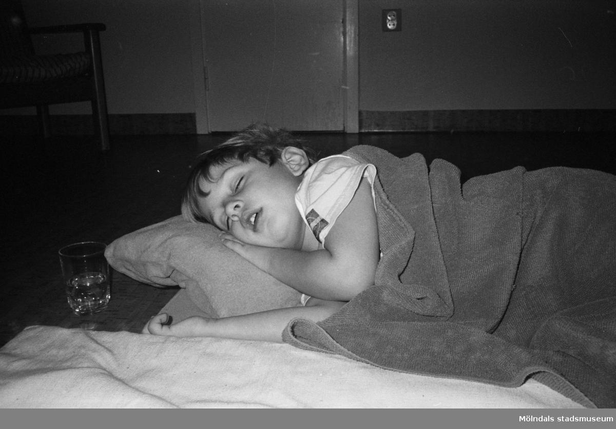 Ett dagisbarn, liggandes på sidan, sover på en utlagd madrass på golvet. Vid sidan om står ett glas vatten. Barnet har en filt på sig. Katrinebergs daghem 1992.