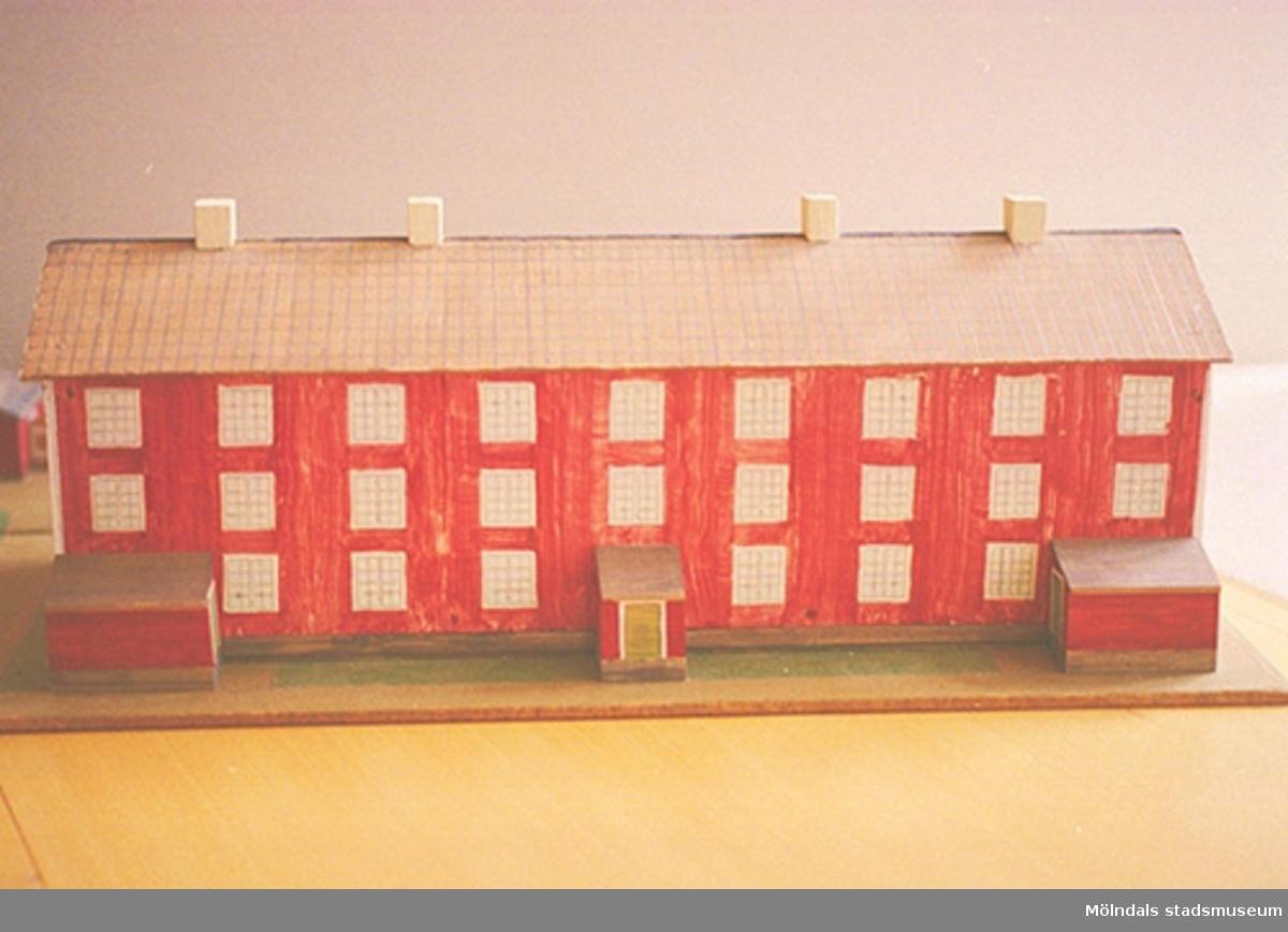"""Ett rött bostadshus med tio fönster i rad, tre våningar högt, och tre entréer. På taket finns fyra skorstenar. Vid sidan av ligger två mindre stugor. Huset är en kopia av """"Byggninga"""" som var arbetarbostäder till Anderstorps fabriker i Lindome. Se även 1994_0992. Harry Bergmans """"gubbar"""" (träfigurer)."""