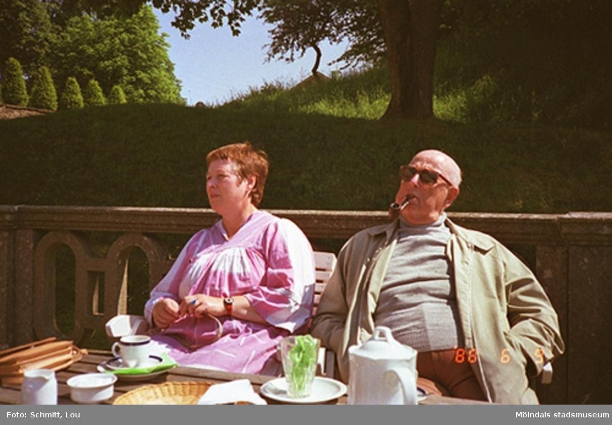 En man och en kvinna sitter på en bänk som står utefter ett staket av sten. Mannen har en pipa i munnen. På bordet, som står framför dem, är det uppdukat för fika. De befinner sig på baksidan av Gunnebo slott. I bakgrunden ser man träd och buskar som tillhör slottets framsida.