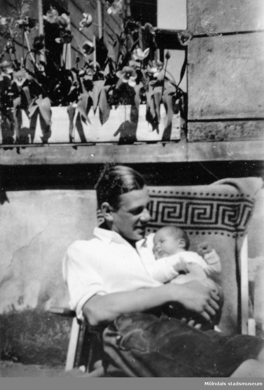 Greve Ultz von Kanitz (make till Ursula von Eckstädt) sitter i en solstol och håller ett spädbarn i famnen. Pommerwitz i Övre Schlesien, 1930-tal.