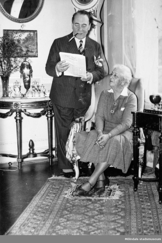 Skådespelaren Anders de Wahl tittar ner i  ett papper, ståendes bredvid Hilda Sparre som sitter i en fåtölj. Gunnebo slott, april 1939.