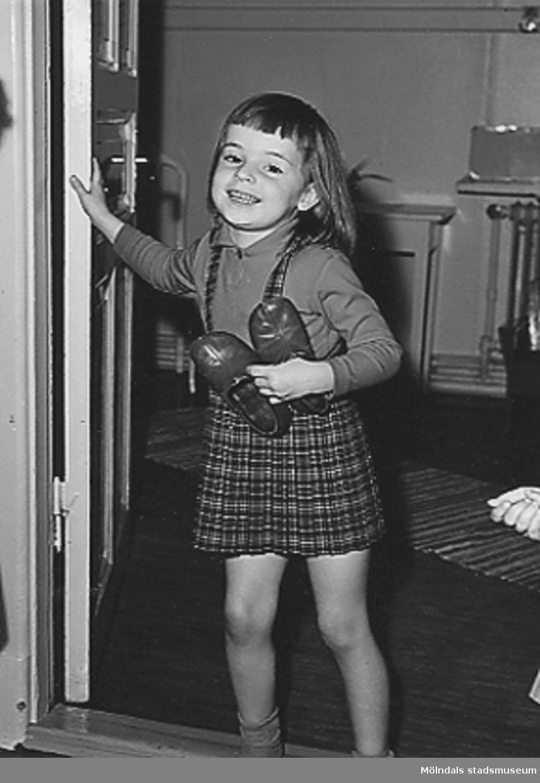 En flicka, med ett par tofflor i ena handen, står utanför en dörröppning vid Holtermanska daghemmet 1953.