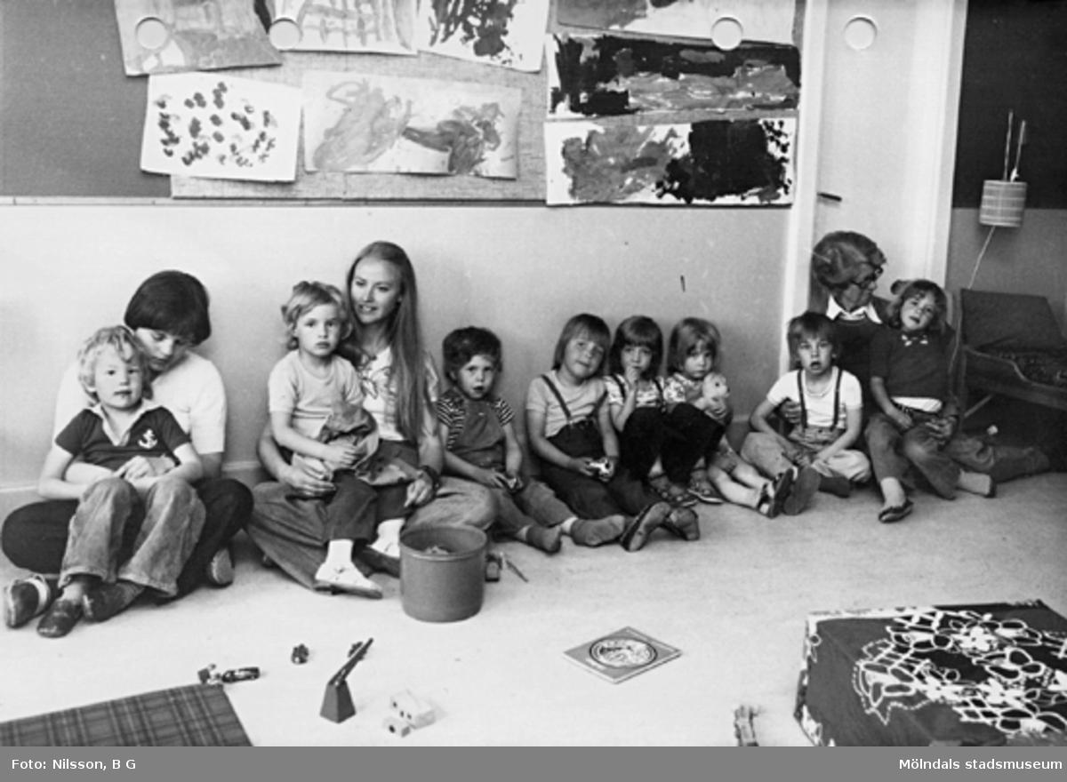 Barn och fröknar som sitter på golvet längs en vägg på Holtermanska daghemmet, maj 1975.