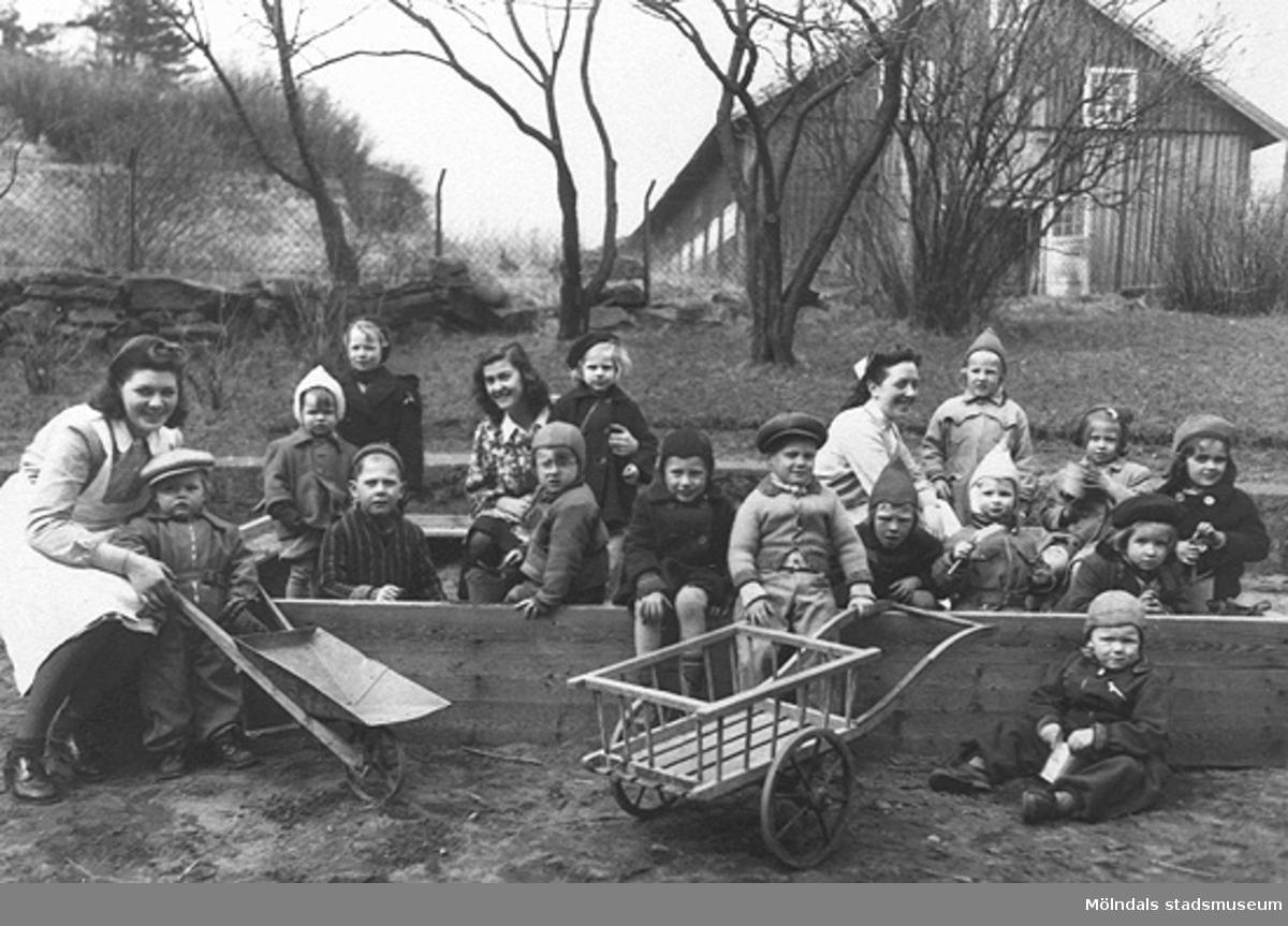 Fröknar och barn vid Holtermanska daghemmet våren 1947. I bakgrunden ses ladugården som hör till Åby Mellangården 3 (Pål-Emils). Ladugården låg söder om Holtermanska och boningshuset ligger norr om gatan.