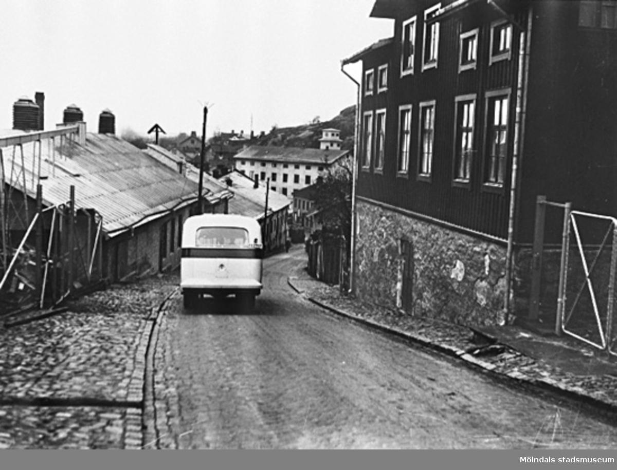 """En buss som kör nedför """"Mölndals Kråka"""" Kvarnbygatan, omkring 1938. På ömse sidor finns Soabs fastigheter.Längst ner på liden ses stadshuset med brandkårens slangtorn (Kvarnbygatan 43)."""