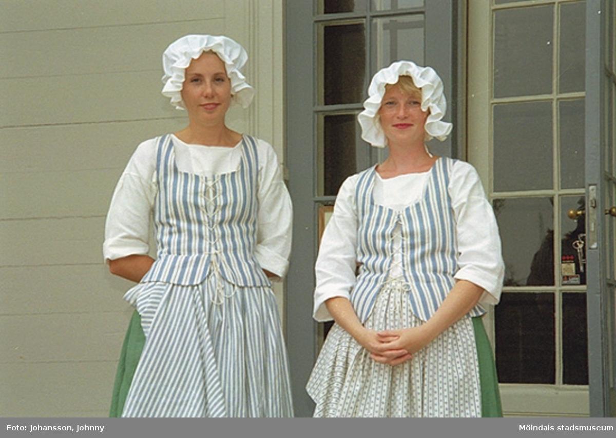 Lotta och Eva står på slottstrappan i tidstypiska kläder (tjänstefolkskläder från 1700-talets slut).