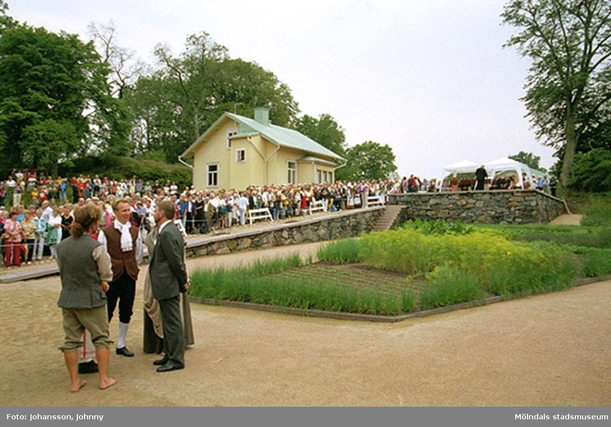 Gunnebopersonal i förgrunden, Staffan Fischer (svarta byxor och vit kråsskjorta) och åskådare i bakgrunden. Det gula huset i bakgrunden är trädgårdsmästarbostaden Solbacken.