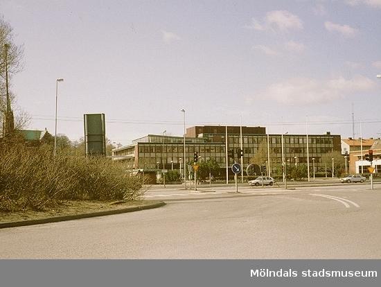 Rondellen mot Göteborgsvägen västerut, mars 1993. I fonden ses Stadshusplatsen och Mölndals stadshus. Relaterade motiv: 2003_0386 - 0387.