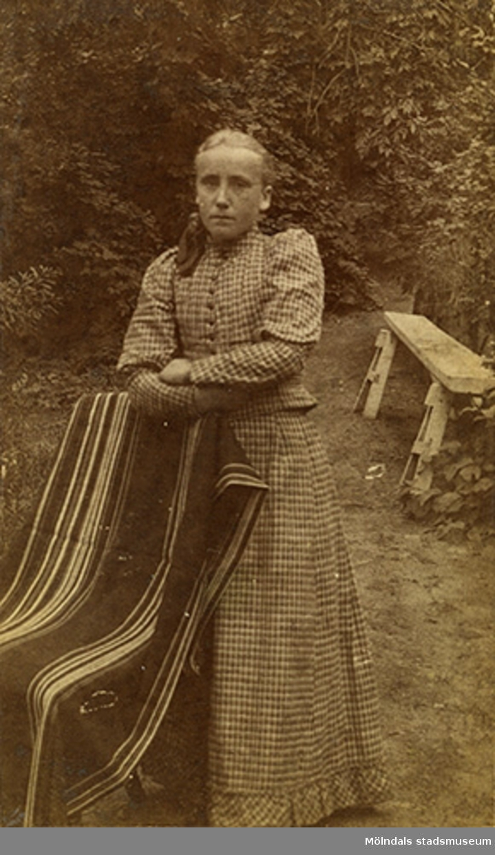 Helfigursporträtt av en stående kvinna, taget utomhus.Namnet Alida Olsson är skrivet på baksidan av fotot.
