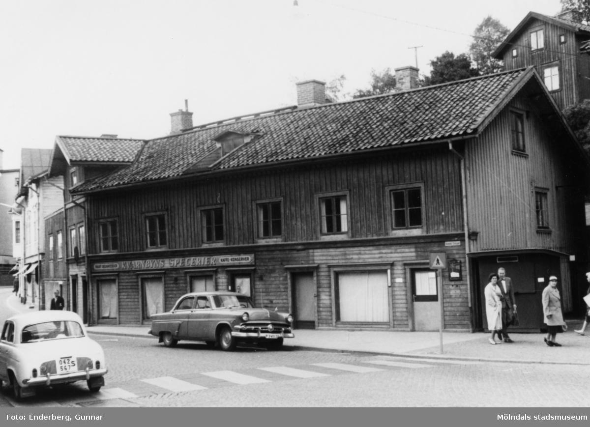 """Kvarnbygatan 39-41 år 1961. """"I detta hus fanns William Olssons velocipedaffär i högra ändan. Bertil och William var bröder och hade var sin cykelaffär. Till vänster i huset låg J. Nundstedts speceriaffär. I övervåningen fanns Stadsingenjörskontorets mätningsavdelning i en f.d. lägenhet. Där arbetade kartriterskor och mätningspersonalen. Jag arbetade själv där från sept. 1957 till 1961 som mätningshantlangare (s.k. pinnpojk). Men jag arbetade mestadels med att kopiera ritningar och kartor. De flesta kopiorna belystes på ljuskänsligt gult papper som sedan framkallades med ammoniak. Fy vad det luktade hemskt när jag tömde upp ammoniak från en plastdunk i den öppna ammoniakbehållaren. Då fick man snabbt springa till det öppna fönstret och kippa efterandan. Någon gång 1961 flyttade vi in i det nya nuvarande Stadshuset. Huset revs i samband med ombyggnaden av Kvarnbygatan."""" / Hasse Hansson"""
