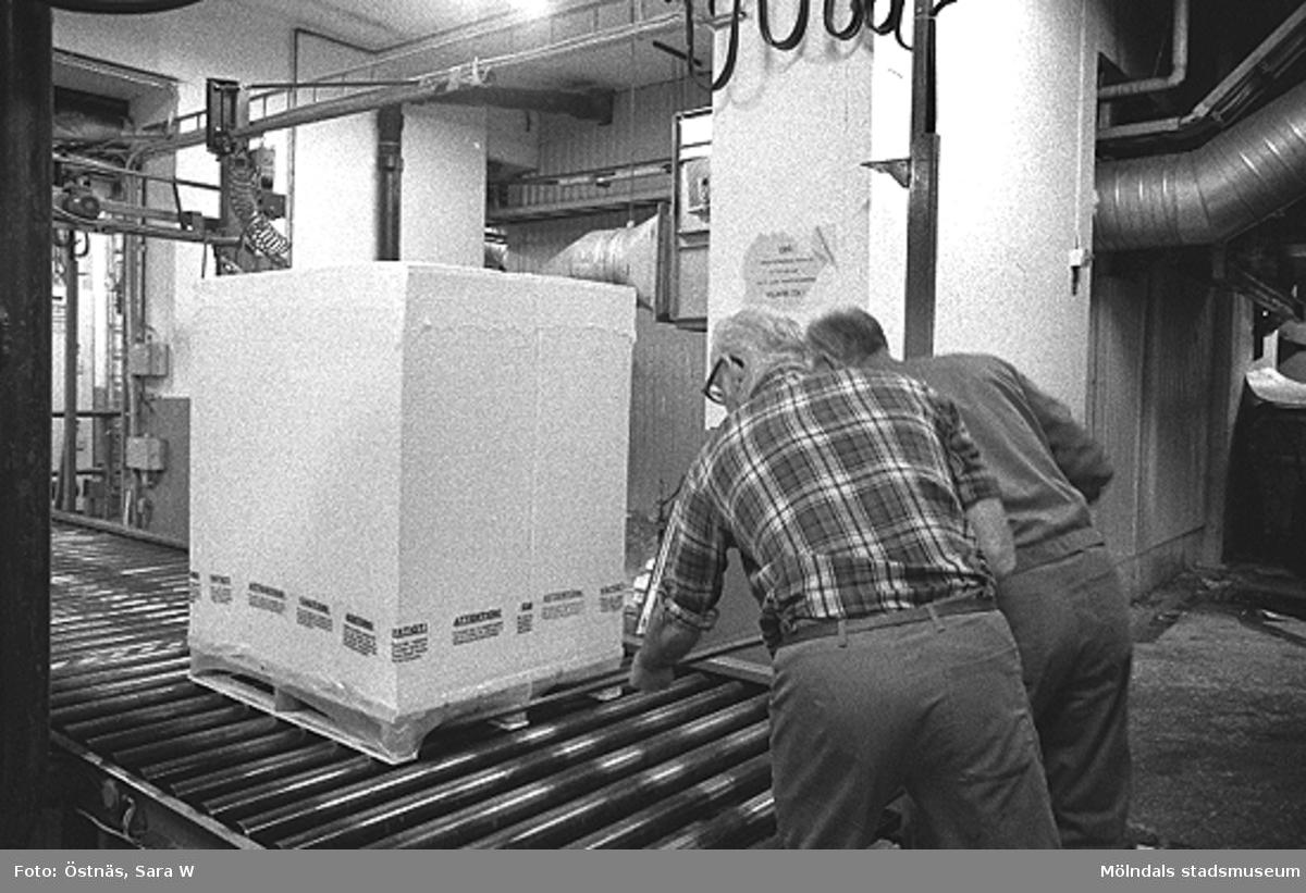Från vänster: Gotthard Olsson och troligen Tage Carlsson arbetar med pallpackning i pappersfabriken, Byggnad 6. Bilden ingår i serie från produktion och interiör på pappersindustrin Papyrus, 1980-tal.