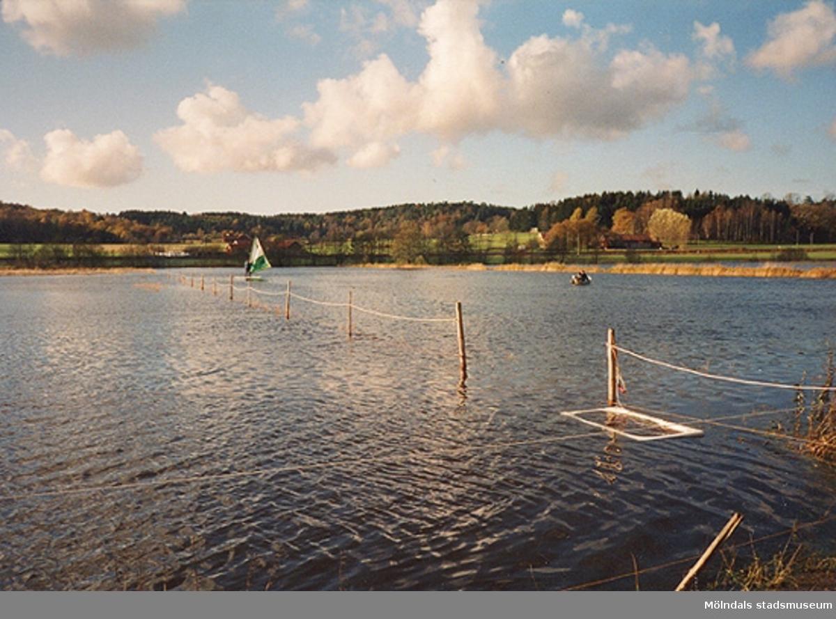 En person som vindsurfar. En båt åker vid sidan. Berget 1:135, Lindome. Oktober 1998.