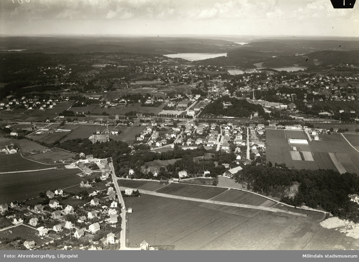"""Flygfoto över Solängen, Fässbergs kyrka, Mölndalsbrområdet och Östra Mölndal, cirka 28 april 1942. I höger bildkant, ungefär i mitten av bilden, syns Yngeredsfors trädgård. Det finns tre olika stämplar bak på fotografiet.Blå stämpel:""""AHRENBERGSFLYG COPYRIGHT Foto: LILJEQVIST""""Röd stämpel:""""FÖRSVARSSTABEN 28. APR. 1942 Granskad och förbjuden för för- säljning, saluhållning och utdel- ning jämlikt Kungl. Kungörelsen  den 31. augusti 1940 (nr 802). ... Granskare""""Lila stämpel:""""Detta fotografi, n:r C1013, får, vid laga påföljd, icke utan särskilt tillstånd reproduceras. A/B FLYGTRAFIK. """""""