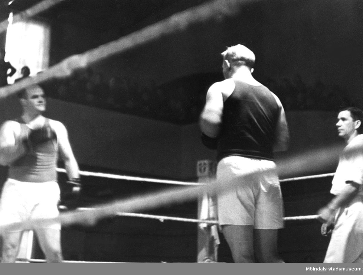 Tungviktsmästare Henry Nicklasson, bosatt i Mölndal, i boxningsmatch mot okänd motståndare, även domare och publik i bakgrunden. HN tillhörde Mölndals Boxningsklubb, och senare Redbergslids.