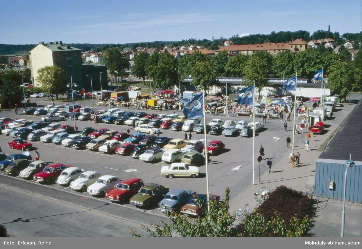 """Så här såg det ut på Nya Torget en lördagsmorgon år 1973, då bönder och affärsfolk kom hit och """"dukade upp"""" sina varor till försäljning.   Till höger syns Konsums stora affärshall.   På torget finns också god plats för parkering av bilar.  I bakgrunden syns biografen Röda Kvarn och affärshusen vid Göteborgsvägen.  Numera är torghandeln flyttad till ett nytt torg i närheten av Åby Stormarknad inte långt från Kungsbackavägen."""
