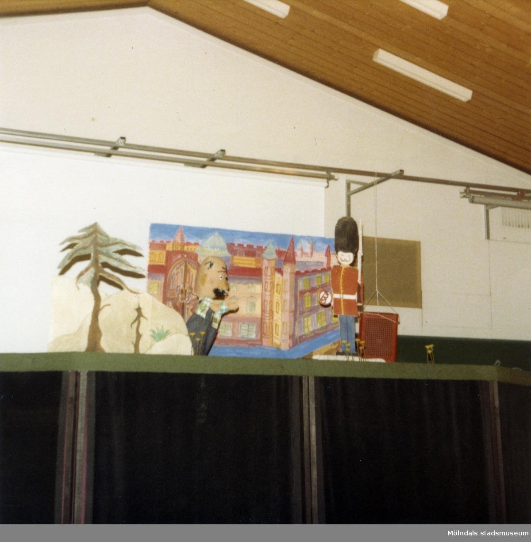 """Föreställning av """"Den förtrollade fisken"""" i Porthällaskolan, Partille d. 25/10 1981. Fotografi ur album tillhörande Blanka Kaplan.  Sagan om den förtrollade fisken är en bearbetning Blanka Kaplan gjort av sagan """"Fiskaren och hans hustru"""". Den gick som dockföreställning under året -81 till början av -82 i TBV-husets lokal på Hagåkersgatan 4 i Mölndal.  Den handlar i korthet om en fiskare som en dag får upp en förtrollad flundra på kroken. Fiskarens hustru begär då att fiskaren ska be flundran att förvandla deras fattiga koja till en nätt liten stuga. Flundran uppfyller önskningen, men hustrun vill snart ha mer och mer och blir med tiden både kejsare och påve. Till sist önskar hon sig för mycket."""