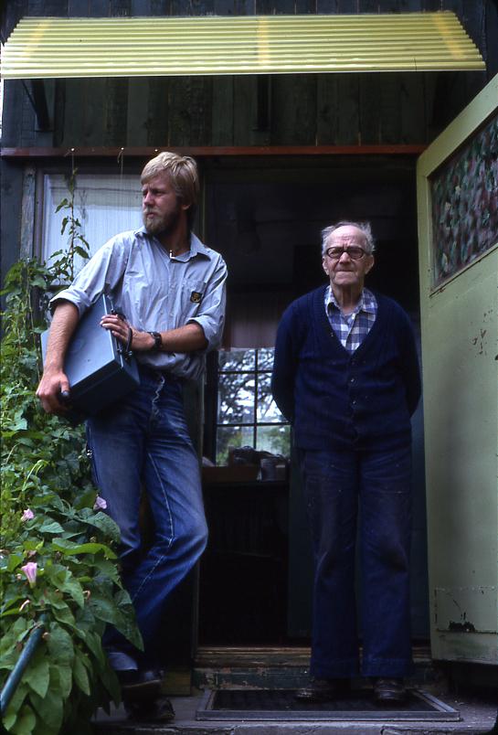 Lantbrevbäraren Mikael Mattsson hemma hos Ernst Svensson i Axelsberg. De står på förstubron till huset. Mikael Mattsson har kassaskrinet under armen.