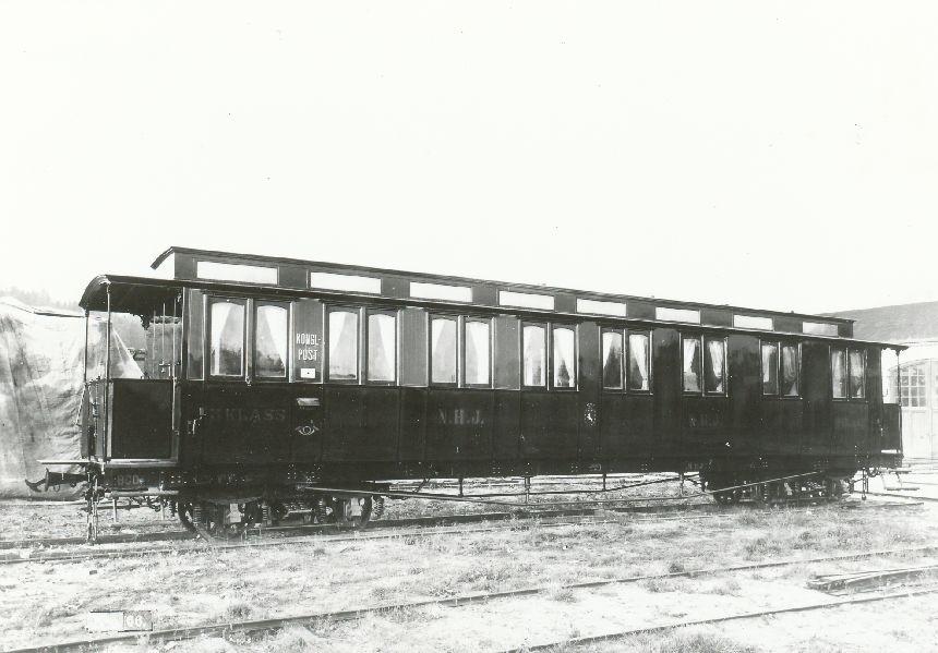 Fotografi föreställande postvagnen NHJ Norra Hälsinglands Järnväg, och postvagnen BCDo 1, tillverkad 1896.