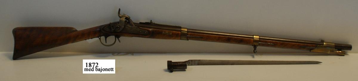 Gevär, 1815 - 1845 - 1848 års reparationsmodell, s.k. tappgevär, slaglås (Tischgevär). Märkt: Tre kronor. Kolven av trä, pipa och mekanism av stål. Beslagen av metall. Pipan räfflad, längd 855 mm. Stickbajonett, längd 560 mm. Kaliber: 19 mm. Vikt: 4,3 kg. Hela längden: 1278 mm.