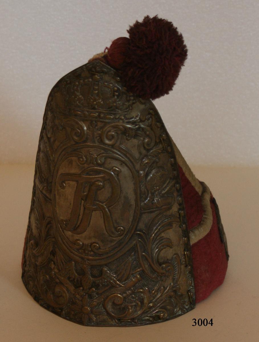 """Preussisk grenadjärmössa, toppformad av kläde, helt röd med gula lister. Tofs av rött ullgarn. Fodrad med grov lärft. Framsidan upptas helt av en vapenplåt av mässing, vanligen med spår av försilvring, av samma höjd som själva mössan. Ytan domineras av ett krönt, i en medaljong anbringat namnskiffer """"FR"""" (Fredericus Rex). På ömse sidor därom en hjälm med hög kam. Nedtill på plåten en på en åttauddig stjärna stående örn, omgiven av heraldiska emblem, särskilt fanor och kanoner. I övrigt fylls ytan av stiliserade palmblad samt volutförsedda akantusblad. På nedre delen av mössan märkas baktill en flammande granat och på sidorna flammor, allt av mässing."""