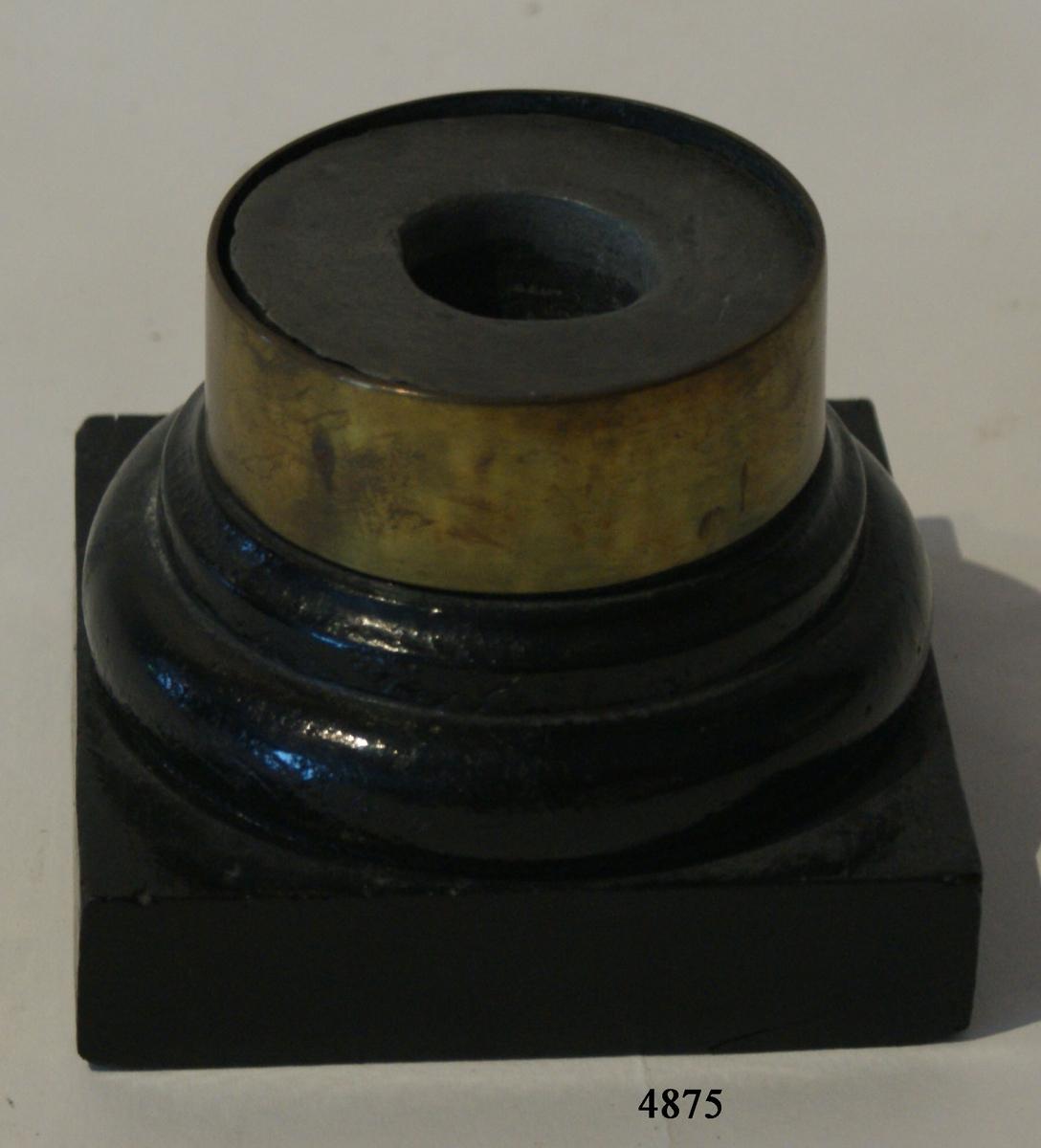 Bläckhorn av trä och bly. Cylindriskt, svarvat och svartmålat. Det är fast vid fykantig svartmålad träplatta. Rummet för bläck invändigt klätt med bly och utvändigt försett med ring av mässing. Plattans dim. = 107 x 110 mm Hornets D = 105 mm