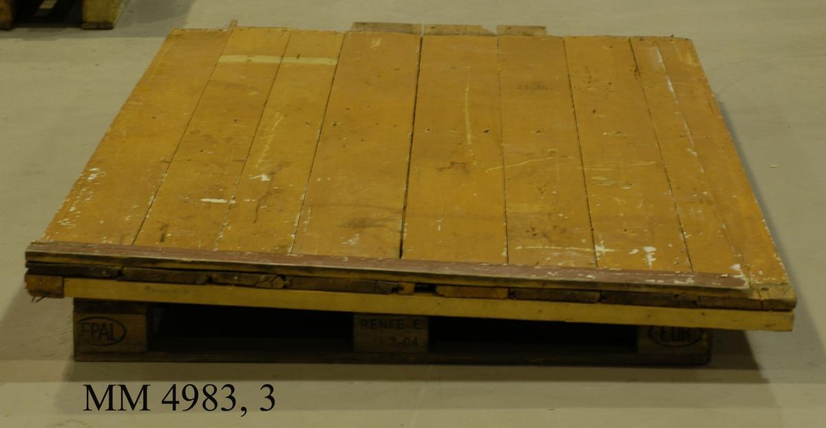 Gamla Tjärhuset å Lindholmen, sektion av innervägg. Skuren genom Repslagarmästarens kammare och inmonterad i den sal i gamla Marinmuseum, som visar utvecklingen inom repslageriverksamheten å ÖVK. Den externa väggytan är gulmålad, med dörrkarmen i grå färg.