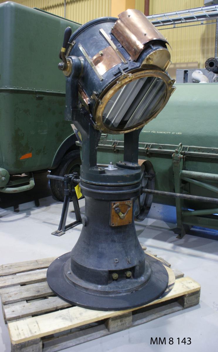 Strålkastare, ljusbåge-, elektrisk, sautter-lemonier. Lampan med tillhörande spegel är inmonterad i en framtill glastäckt trumma, som är vridbar. Framför glaset en metallring med lins. bestående av sju slipade vertikala glasstrimlar. Trumman vilar medelst tappar i  två armar, fästade på en rund platta på stativ. I plattans centrum en axel, som är lagrad i stativet, varigenom strålkastaren kan vridas runtom. Stativets övre del cylindrisk, den nedre konisk och försedd med en sarg med bulthål för fastsättning. Märkning: L. SAUTTER LEMONNIER & C IE PARIS 1883  No  422 PROJECTEUR NANGIN M TE  S.G.D.G. Märkning i vitt: No 3.  Bokstäver, gjutna upphöjda i pivoten: P N Text på spaken: Arret Marche