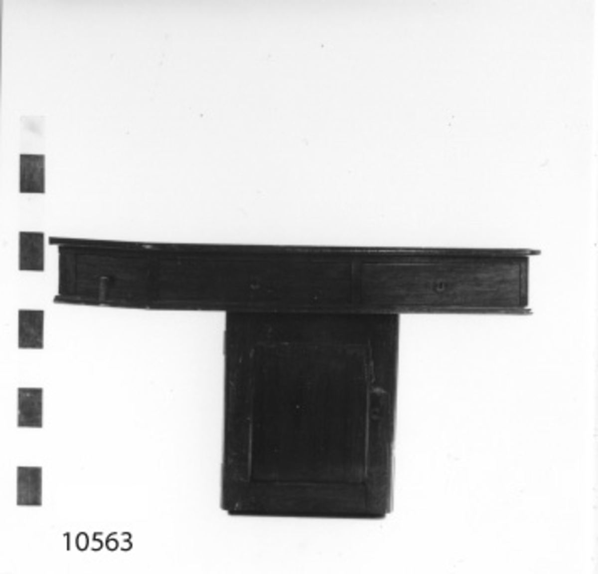 Skrivbord av furu i fanér, mahognybetsat. Försedd med en lös hurts och tre lådor, en hörna snedskuren.