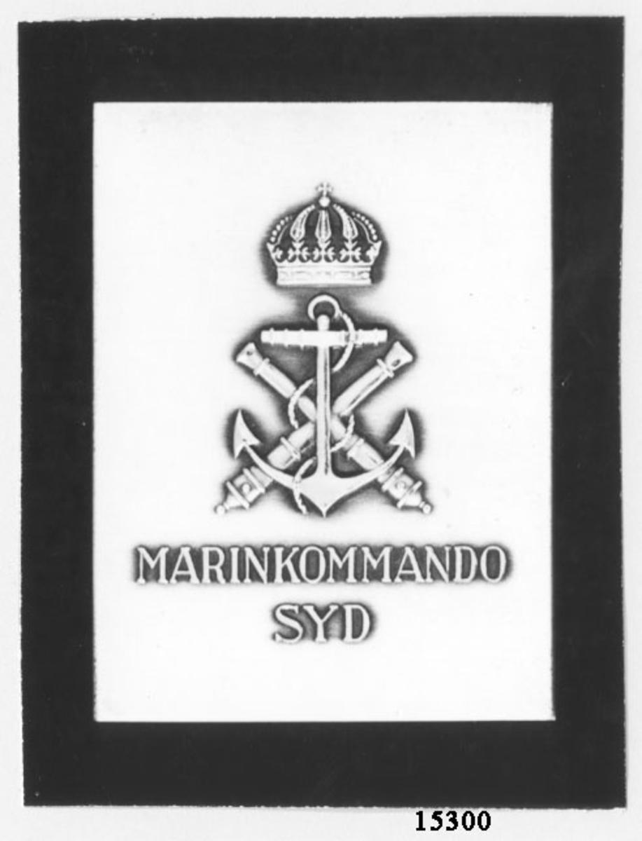 Sköld silver sv bakelit marinens emblem Svart rektangulär platta med på åtsidan matt, rektangulär silverplatta, med marinens emblem blankt och över detta en sluten kunglig krona. Under står: MARINKOMMANDO SYD. Såväl text som märke blankt. På frånsidan fyra fästhål för silverplattan, annars slät.