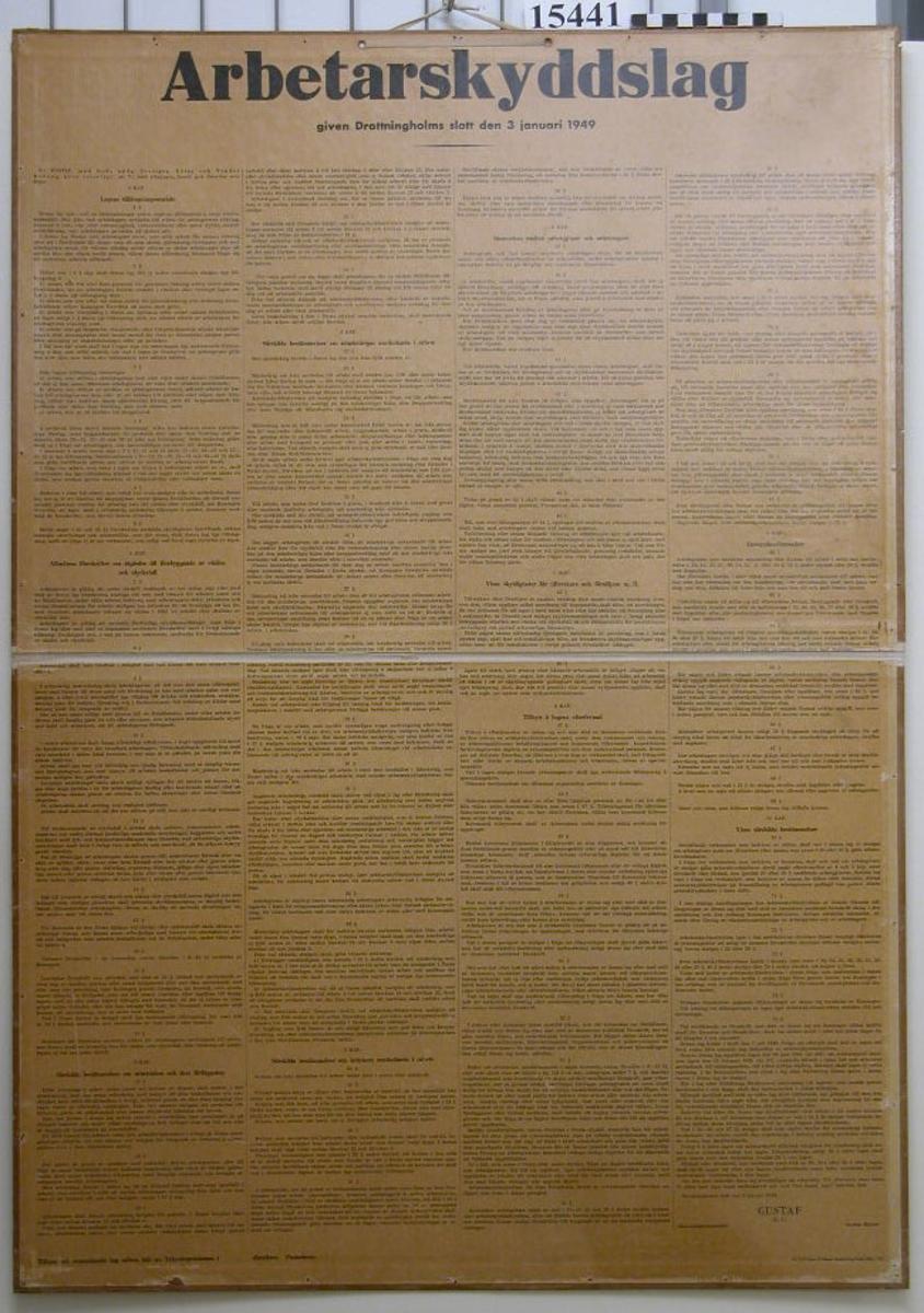 """Vikbar plansch på mitten. Fet text överst på planschen """"Arbetarskyddslag"""" under denna med mindre text: """"Given Drottningholms slott den 3 januari 1949"""". Textpappret är uppklistrat på kartong."""