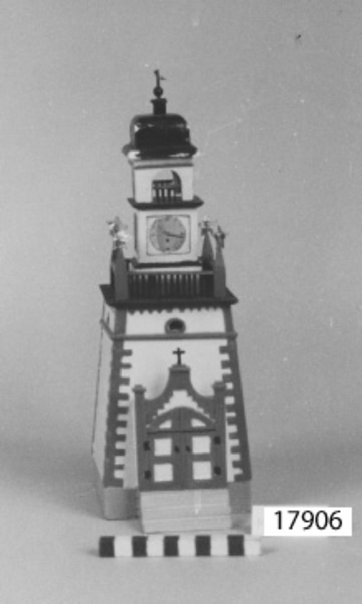 Modell av masonite föreställande Amiralitetsklockstapeln, Karlskrona. Mindre detaljer av plywood ock massivträ. Modellen är målad i blek gul botten, hörnor och ornament i mörk gulockra, tak och staket i svart. Liten örlogsflagga på taket av papper, samt urtavlor av papper, urklippta ur tidning. Sockel och trappa i grått. Guldstjärnor av papper på de små tornen. Modellen går att dela i tre sektioner. I sektionen med urtavlorna finns på insidan en fastklistrad lapp med kort beskrivning samt namn på tillverkare och ägare.