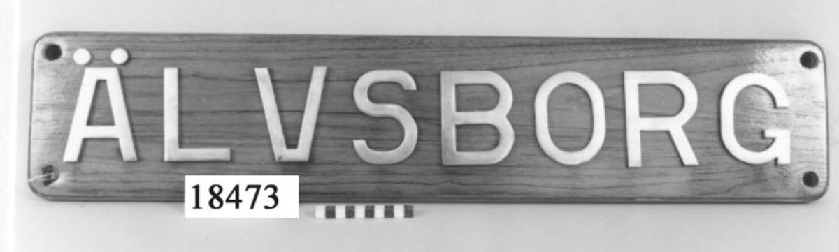 """Namnbräda teak, rektangulär. Bokstäver av polerat stål """"ÄLVSBORG"""" 15 mm bredd, fastskruvade på plattan. Hål i varje hörn för uppmontering."""
