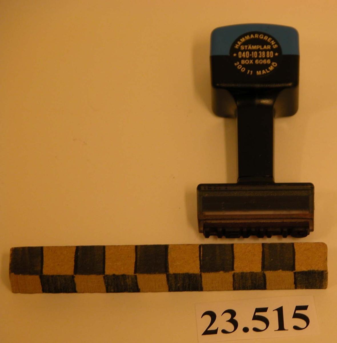 Stämpel bestående av svart och blått plasthandtag, rektangulär form. Stämpelfot rektangulär med gummidyna. Text: HEMLIG. (Stämplas med rött). Rund svart etikett på handtaget anger tillverkare: HAMMARGRENS STÄMPLAR *040-103880* BOX 6066 20011 MALMÖ. Instansning i plasten: VISION.