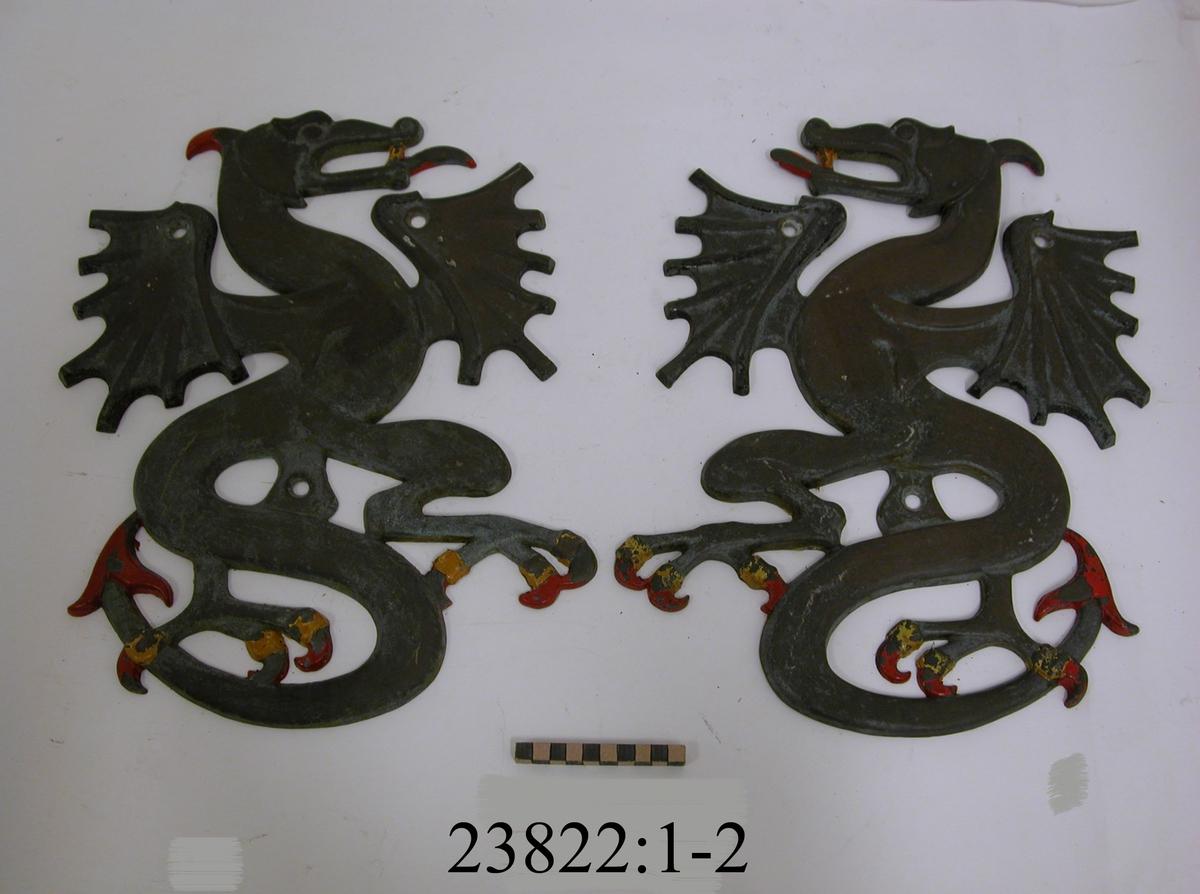Drake gjuten i brons, stående och färdig till anfall. Klor, tungor och svansspetsar målade i färgerna rött och gult. Övriga partier metallfärgade. Tre hål för uppmontering.