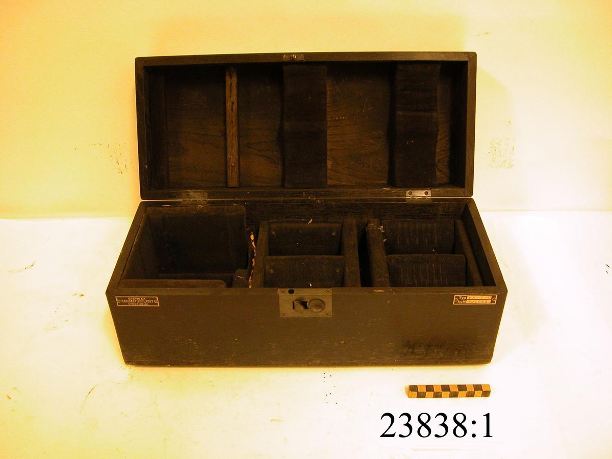 Svart, rektangulär låda av trä med sex stycken fack fodrade med svart sammet. I lådan förvaras instrumentets fem komponenter MM 23838: 2-7
