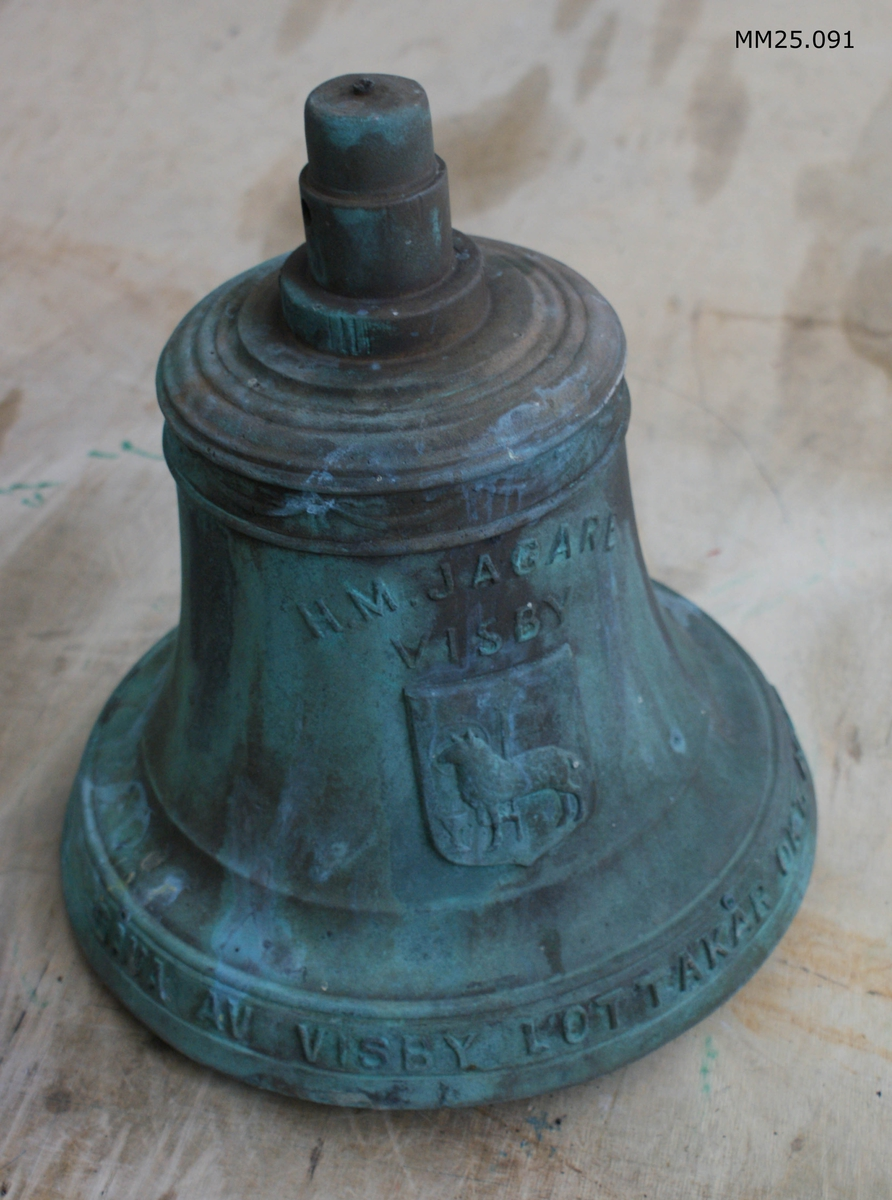 """Skeppsklocka av brons med viss patina. Inskription """"HM JAGARE VISBY"""" över Visbys stadsvapen. Inskription längs klockans botten: """"GÅVA AV VISBY LOTTAKÅR OKT 1942""""."""