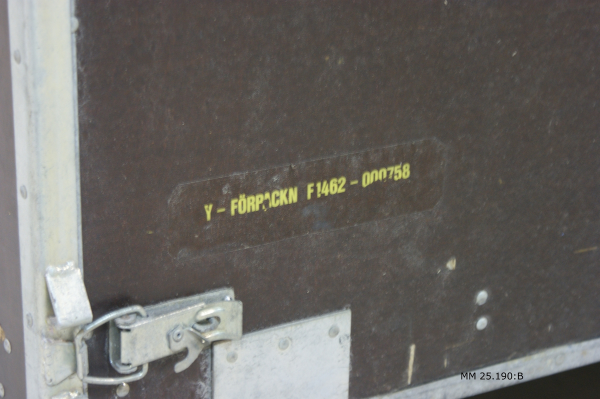 """Brun trälåda med metallskodda kanter och härn. Lådan består av två likadana gångjärnsförsedda halvor som utgör varsin lång och kortsida. De vika runt ett spår i lådans bottenplatta och sätts ihop med hjälp av haspar. Märkning: """"""""Hydrofonvinsch HKP 4"""" och """"Y-förpackn F1462-000758""""."""