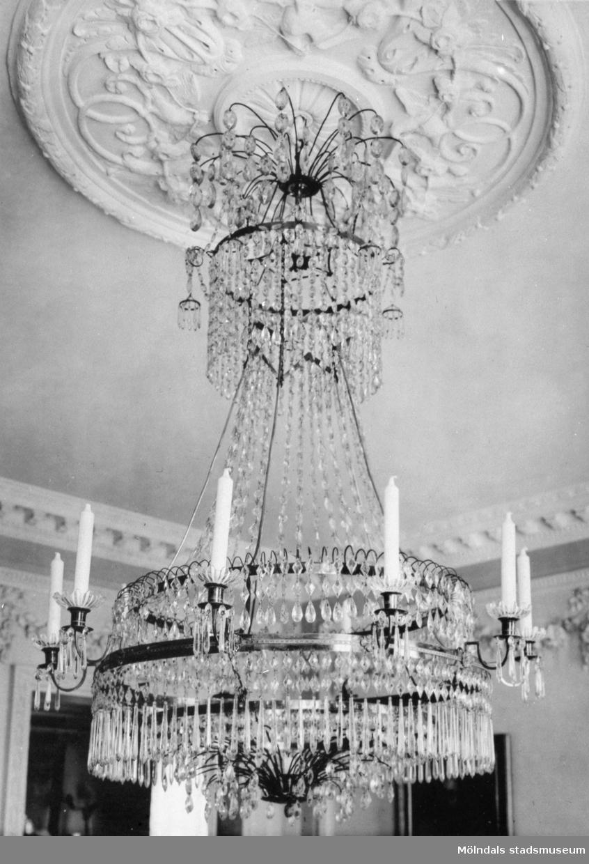 Takkrona med slipade kristallprismor och plats för ljus. Gunnebo slott, 1930-tal.