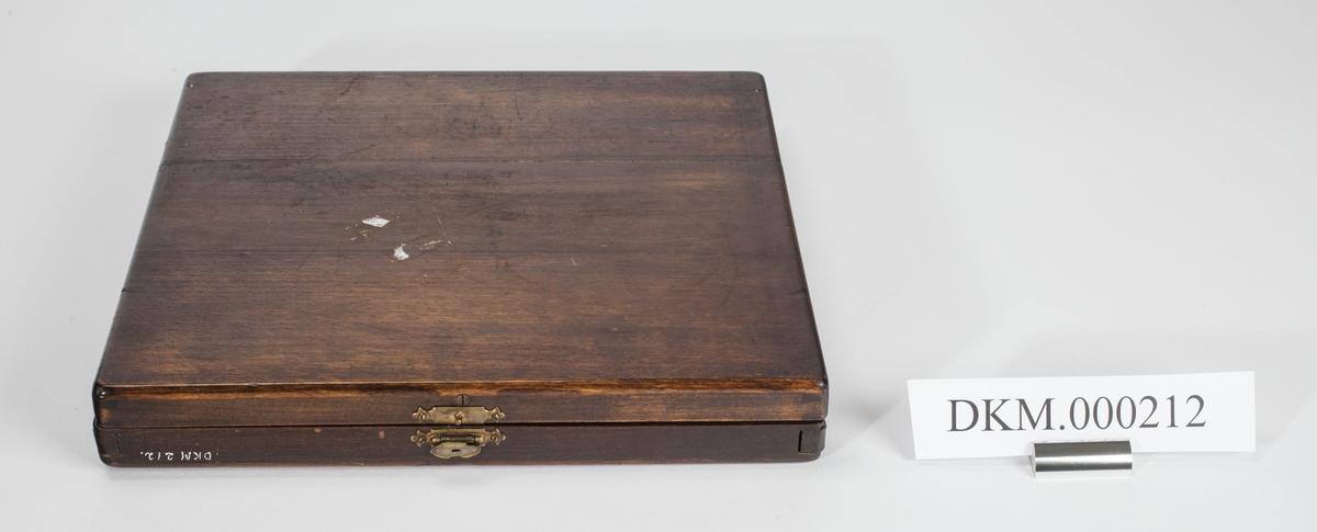 Flat rektangulær kasse med lokk. Liten metallås foran til å holde igjen lokket.