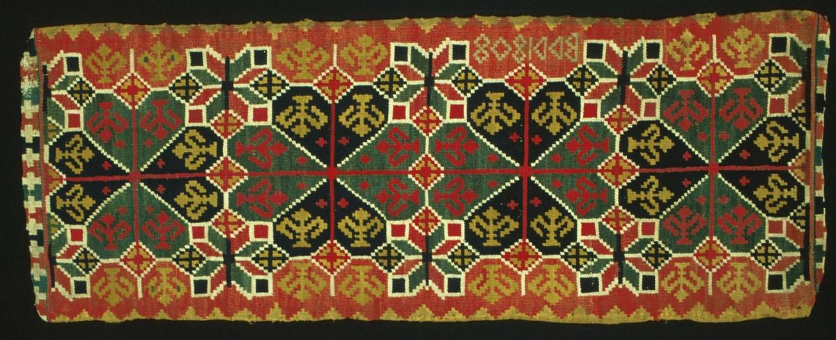"""Dyna i rölakan (halvstygn). Motiv med fyra stycken runduddiga stjärnor med en lilja i varje vingfält. Mellan dessa stjärnor är två spetsuddiga stjärnor placerade mitt för varandra. Fyllnadsfigurer i form av olika runduddiga stjärntyper och liljor. Utefter vardera långsidan löper en bård av trekanter. På kortsidorna en bård i form av kors. Bottenfärgen är röd, bottenfärgen i de runduddiga stjärnorna är blå och grön. Mönsterfigurernas färger är blå, gul, grön, röd och naturvit. Dynan är sekundärt fodrad med svart bomullssatin. Varp i 2-trådigt s-tvinnat lingarn, 5 trådar/cm. Inslag i 1-trådigt s-spunnet ullgarn, 2 trådar tillsammans, 16 trådar/cm. Märkt på baksidan med tyglapp med texten: """" Landstinget  N° 67 a  Oxie h-d.""""."""