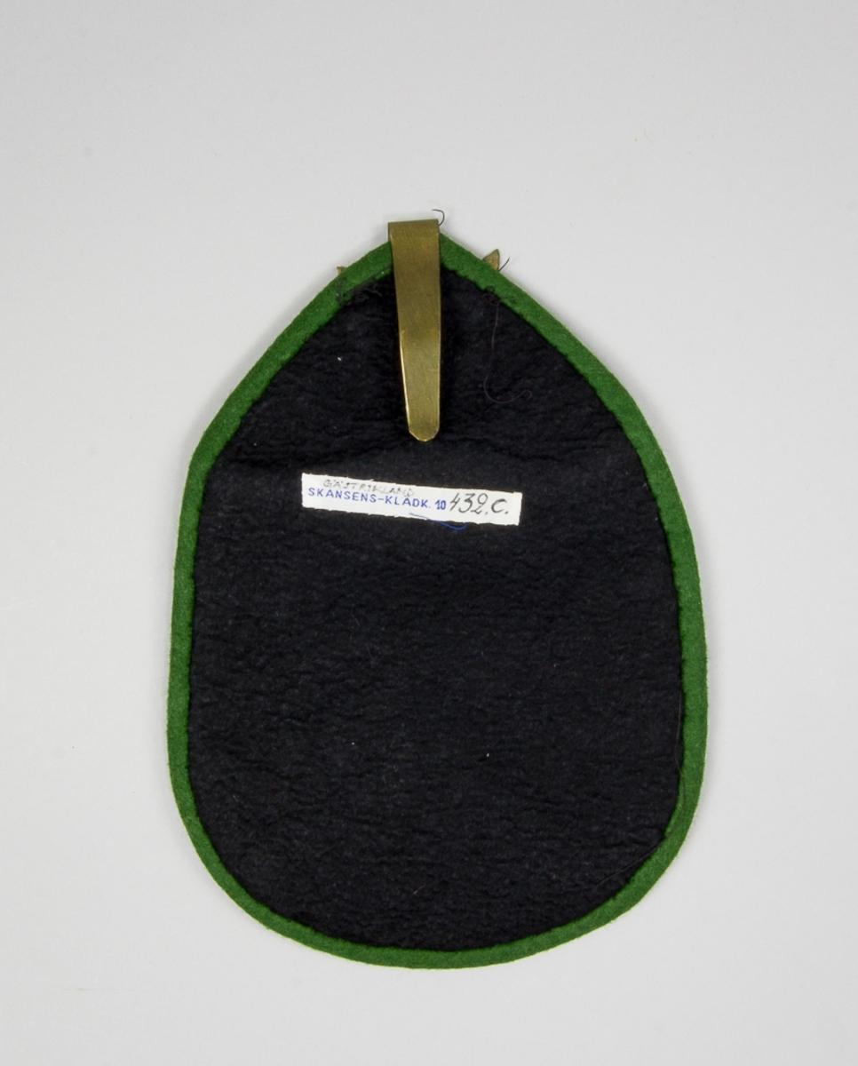 Kjolsäck till dräkt för kvinna från Ockelbo socken, Gästrikland. Modell med avskuret framstycke. Fram- och överstycke av svart ylletyg med applikationer av ylletyg i vinrött, gult, grått och grönt, fastsydda med stjälkstygn i svart sytråd. Motiv: urklippt uppochnervänt hjärta omgivet av olika former. Kantat med remsor av det gröna tyget. Framsidan fodrad med svart fodersidentyg, fabriksvävt. Bakstycke av svart ylletyg. Fastsydd hake av mässingsplåt med hamrad dekor och utsågade hål.