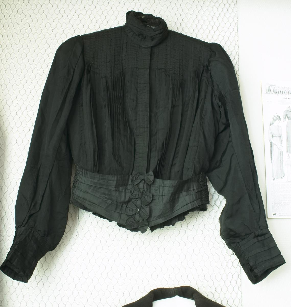 En svart silkebluse med belte. Åse Tomine Torkildsdatter Sjølingsatd har eid blusa og lua.