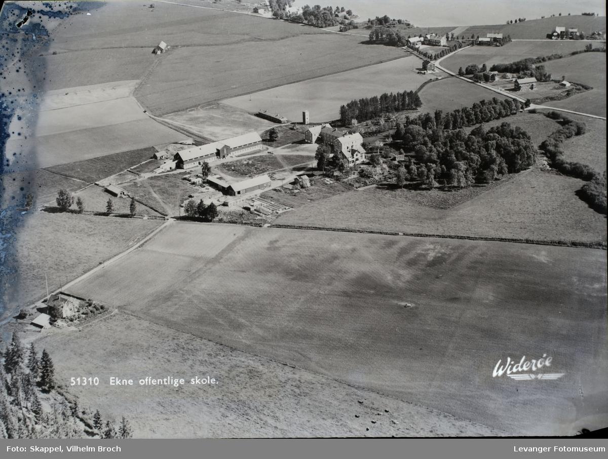 Fjellanger og Widerøe`s flyfoto av gård,gårdstun, åker og landskap.  Institusjonsbygning