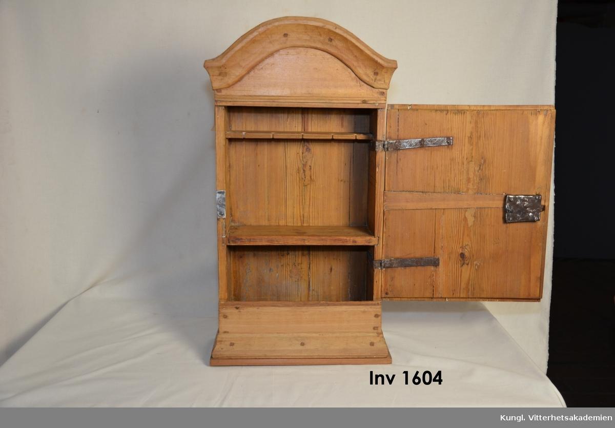 """Hängskåp furu utan färg på grund av att skåpet är avlutat.  Formen rak, bågformad krönlist , överstvcke bågformat. Daterande årtalet  """"anno 1831""""  kan skönjas på skåpets framsida. Försedd med enkeldörr  med nyckelskylt av järn i rombisk form. Gångjärn och upphängningskrok på baksidan av järn.Inne skåpet finns två hyllor, den översta med urtag för fem skedar i form av laxstjärformade urtag. Skåpet hopfogat med hjälp av tränaglar.   fr. Rickebasta Alsike sn.Uppland"""