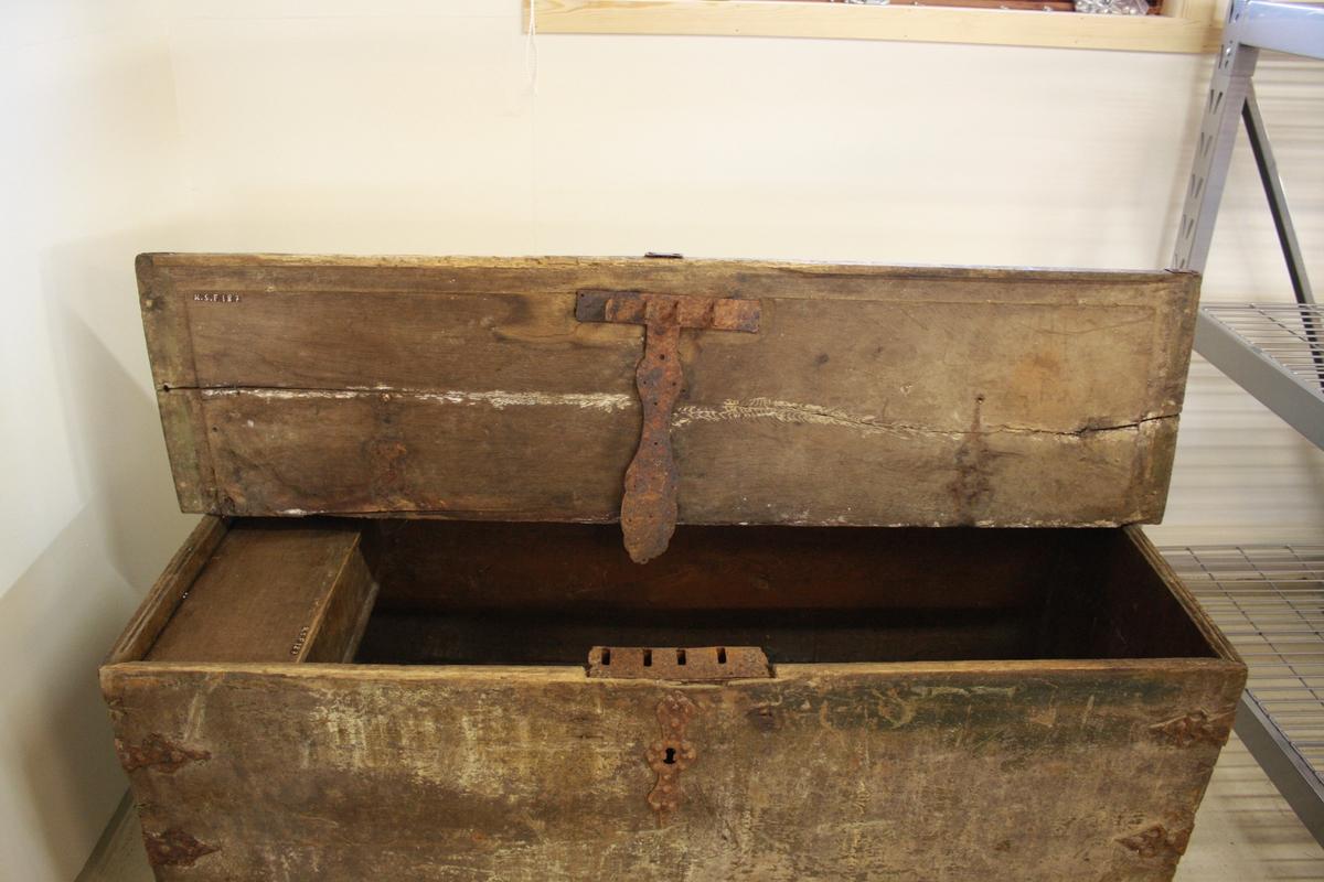 Stor kiste med flatt lok. Har truleg blitt nytta som kornkiste. Metallbeslag over lås og hjørne. Lås øydelagt. Loket har knekt i to delar. Inni har kista ein leddik med lok.