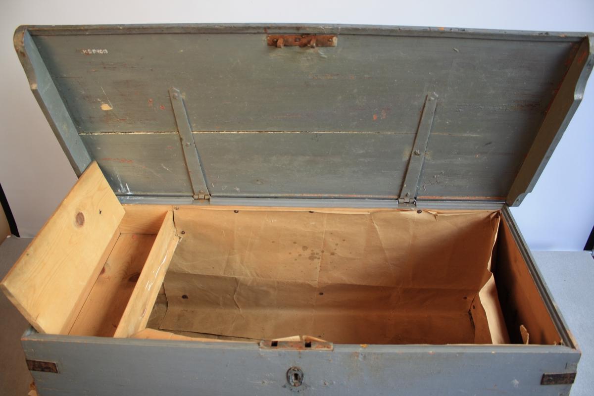 Skipskiste med flatt lok som buer innover. Metallhank på kvar side. Blåmålt med ein svart rand nede. Hjørna har metallbeslag. Sett saman ved sinking. Inni har kista ein leddik med lok. Innsida er dekt med gråpapir.