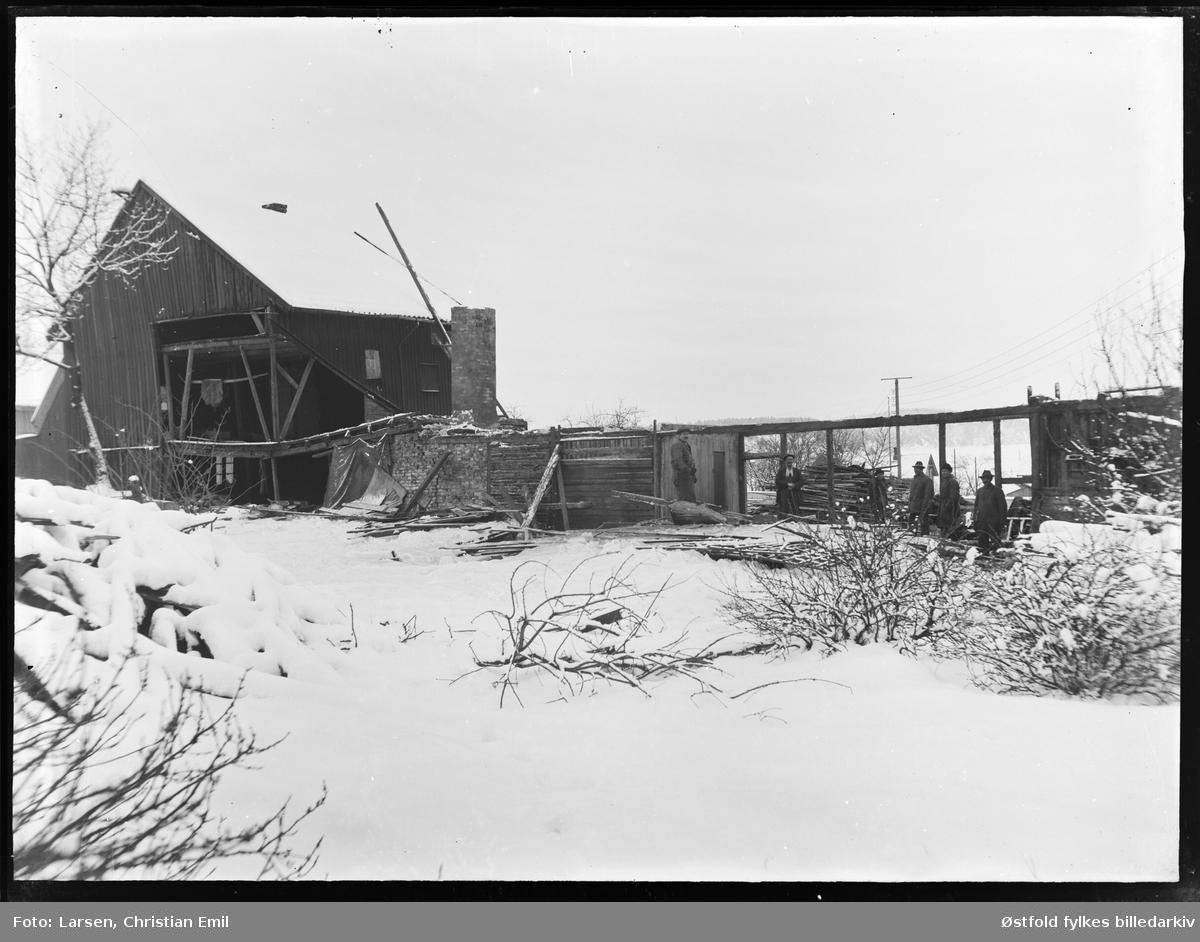 Riving av garveriet i Glengsgata 14 i Sarpsborg januar 1927.  Sarpsborg jernbanestasjon og tømmerkrana på Opsund i bakgrunnen. Ukjente personer.