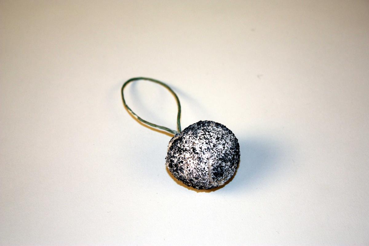 Juletrekule, overstrødd med gråtttsølvaktig glitter som liknar kråkesølv.