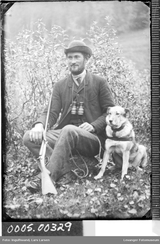 Portrett av mann med kikkert, gevær og en hund.